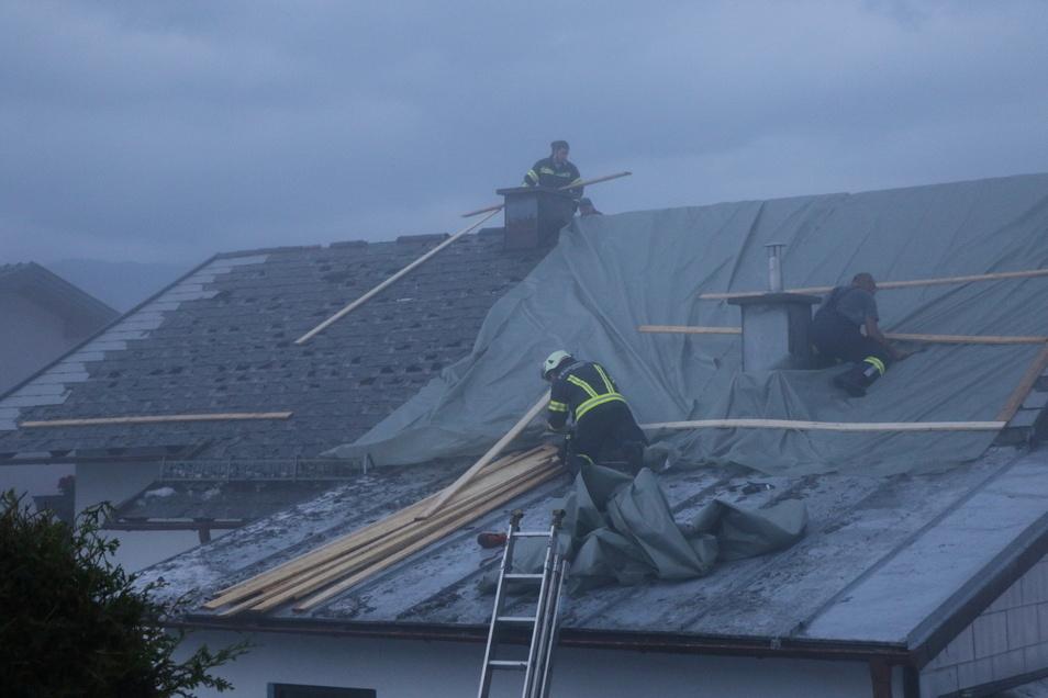 Österreich, Salzburg: Feuerwehrleute arbeiten auf einem beschädigten Dach.
