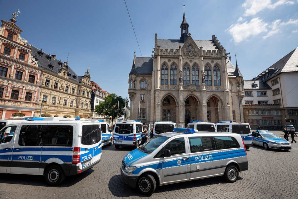 Polizeifahrzeuge stehen nach einer Bombendrohung vor dem evakuierten Rathaus in Erfurt.