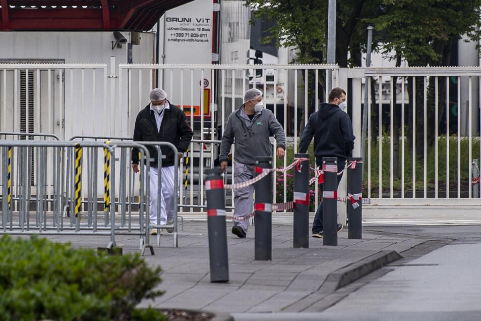 Mitarbeiter des Fleischbetriebs Tönnies tragen Masken, als sie aus einem Werkstor kommen.