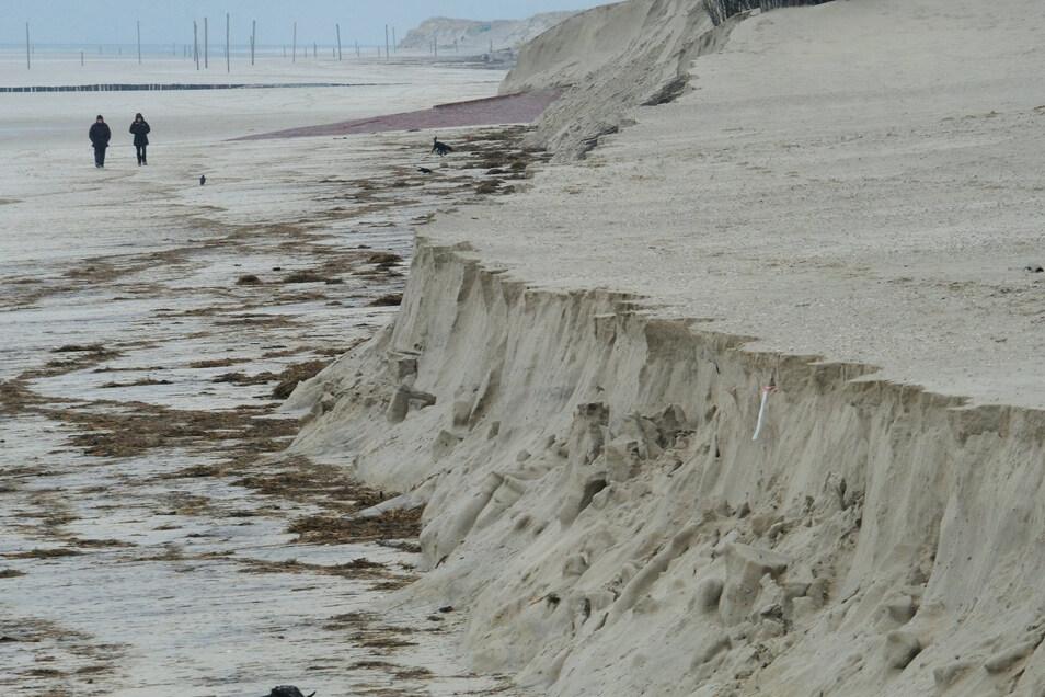 Besucher spazieren an der Abbruchkante des Strandes.