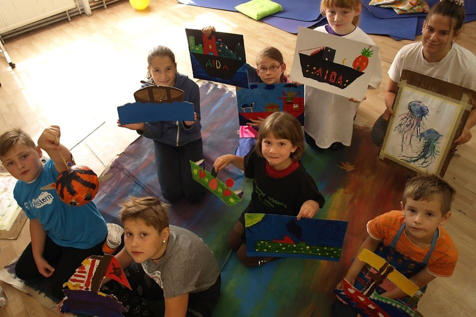Die Teilnehmer der Kindermalwerkstatt zeigen stolz ihre Arbeiten.