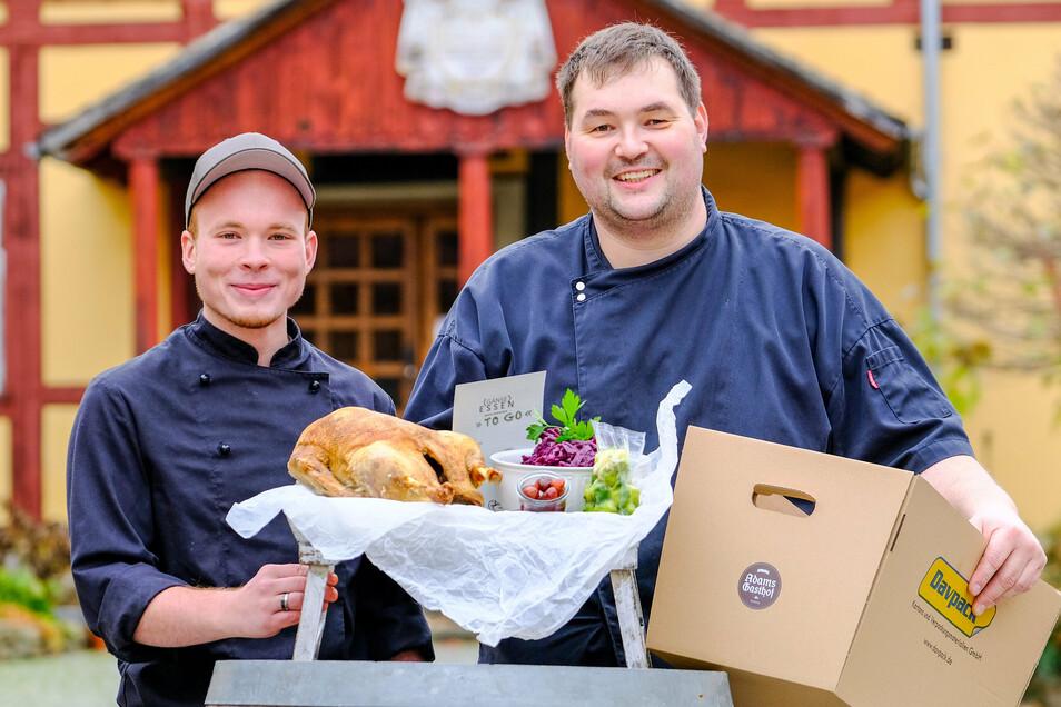 Freuen sich mit vielen Kollegen, dass die Küche nicht kalt bleibt: Koch Paul Schunk (links) und Thomas Eckelmann (Souschef) am 11.11.2020 mit dem Gans-To-Go- Paket vor Adams Gasthof in Moritzburg.