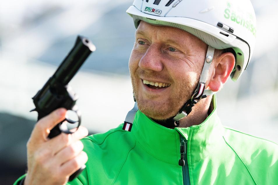 """Dienstagmorgen in Dresden: Michael Kretschmer (CDU), Ministerpräsident von Sachsen, hält vor Beginn der Auftaktveranstaltung zur Aktion """"Mit dem Rad zur Arbeit"""" eine Startpistole in der Hand."""