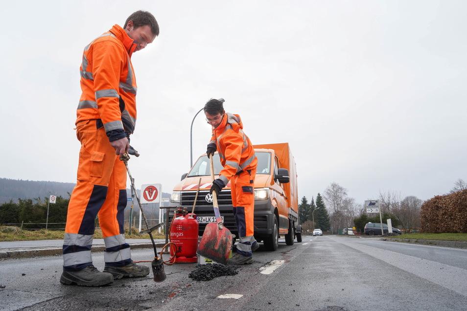 Benjamin Semprich (l.) und Marcel Schneider von der Straßenmeisterei Bautzen sind derzeit häufig an Straße zwischen Wilthen und Tautewalde im Einsatz. Die Verfüllung der Schlaglöcher mit Trockenbitumen hält wegen der Temperaturschwankung nur kurz.