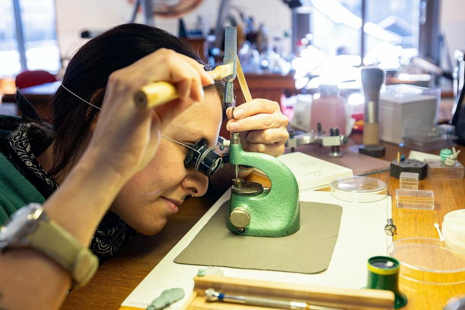 Es läuft jetzt ruhiger bei Tutima in Glashütte, aber es läuft: Finisseurin Stefanie Luce bearbeitet einen Winkelhebel, der am Aufzugsmechanismus einer Luxusuhr seinen Platz hat.