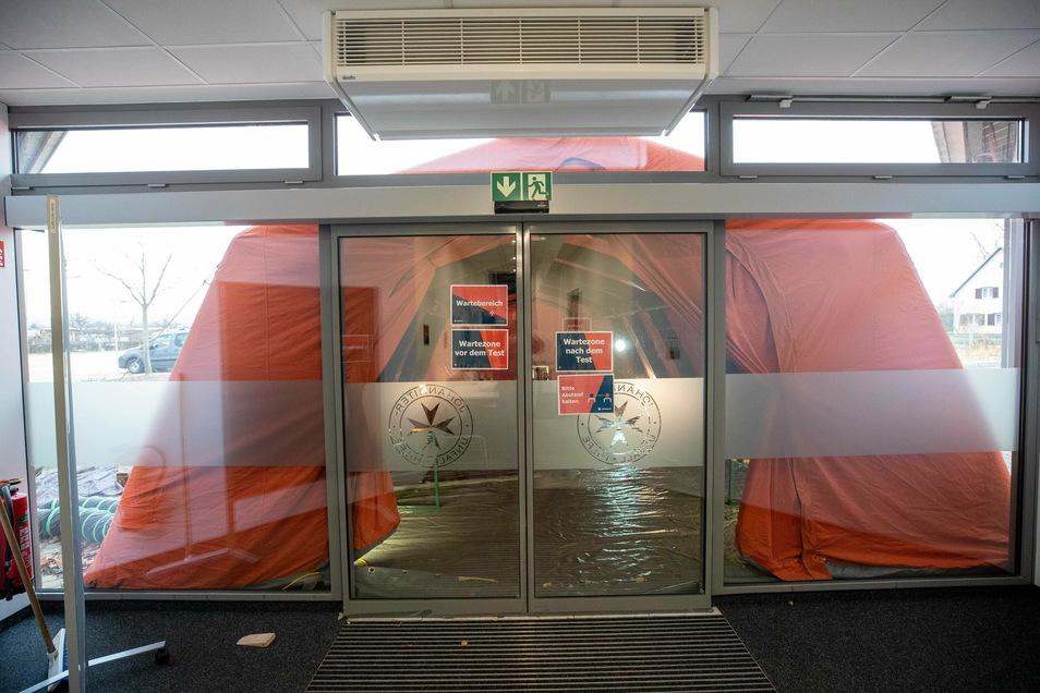 Durch die Tür geht es ins Gebäude, wo der Abstrich für den Test genommen wird.