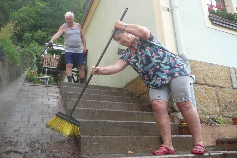 Sturzbach vor der Haustür: Brunhilde Huke und Werner Wengler entschlammen ihr Grundstück in Postelwitz.