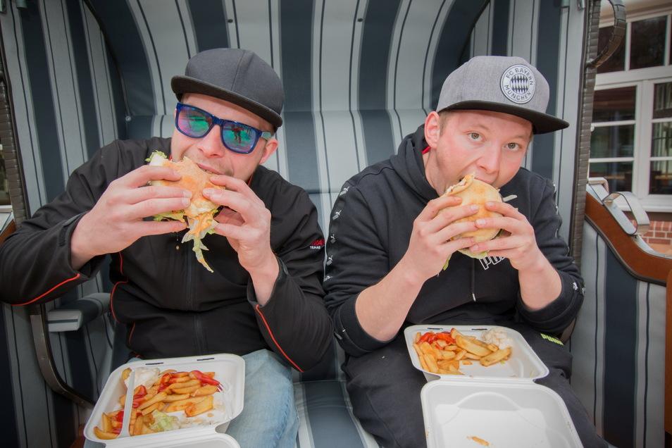 Alexander Zele (links) und Tom Viezens genießen im Standkorb einen frisch gegrillten Burger.
