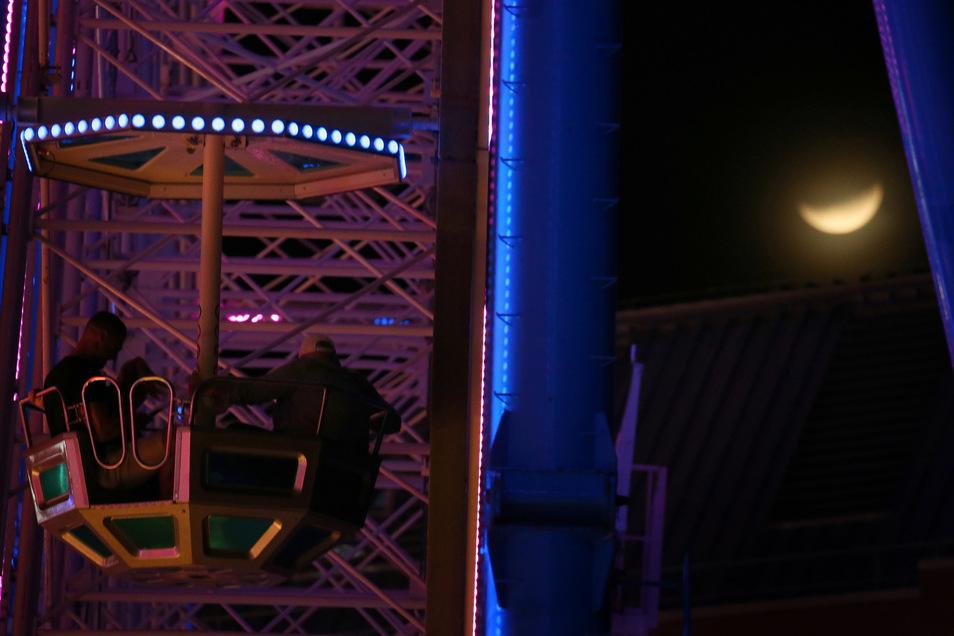 In Würzburg war der Mond hinter dem Riesenrad des Kiliani-Volksfestes zu sehen.