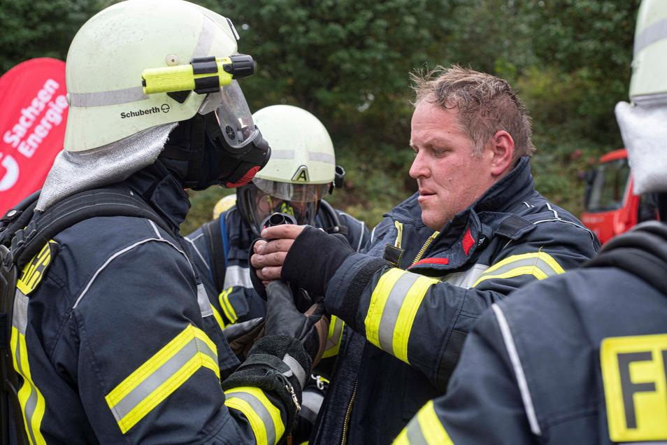 Frank Biber von der Ortsfeuerwehr Neschwitz hilft Kameraden beim Anlegen des Atemschutzes.