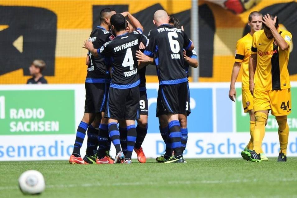 Frankfurts Spieler jubeln nach dem 0:2 während sich Dresdens Cristian Fiel (r) an den Kopf fasst.