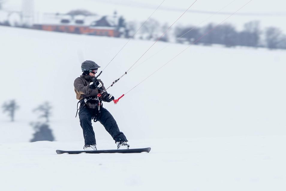 Snowboard, Gurtzeug und eine ganze Menge Können gehören zu dieser rasanten Fahrt übers verschneite Feld.