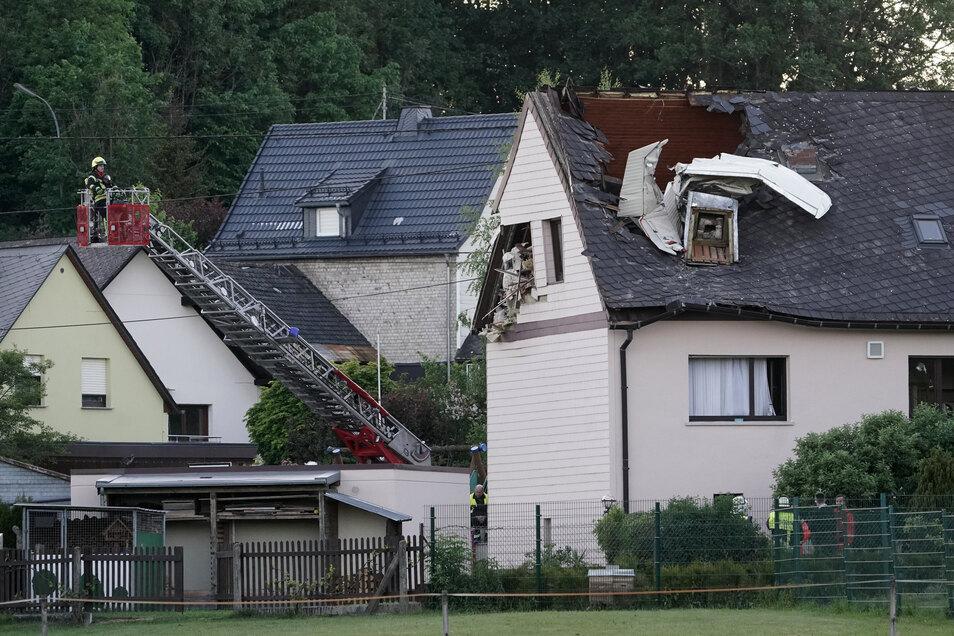 Wrackteile des Kleinflugzeuges ragen aus dem Dach