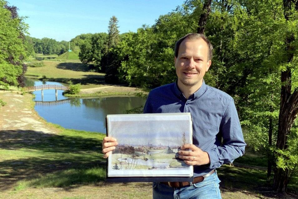 """Parkleiter Claudius Wecke am Branitzer Hermannsberg mit Blick zur Pückler'schen Landpyramide; hier """"der Chef"""" mit einer Zeichnung aus Pücklers Zeit."""