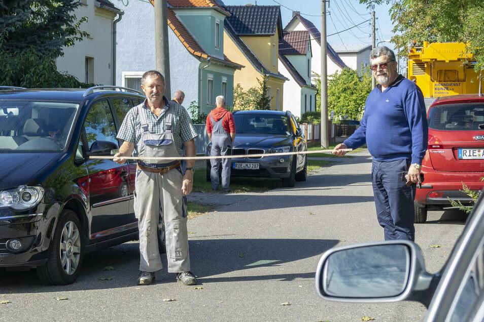 Breit genug für den Rettungswagen, zu schmal für einen Autokran: Parkende Autos haben am Montag die Zufahrt zu einem in Zeithain geplanten Funkmast-Standort blockiert. Anwohner hatten auch den AfD-Abgeordneten Carsten Hütter (r.) dazu geholt.