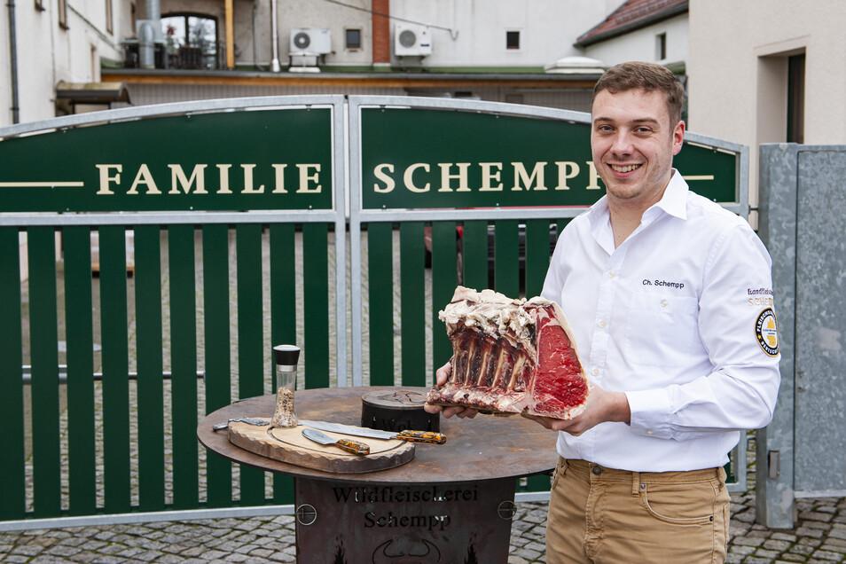 Meisterschafts-Veranstalter Christoph Schempp mit Dry Age-Rinderrücken vor der rustikalen Firmen-Feuerplatte.