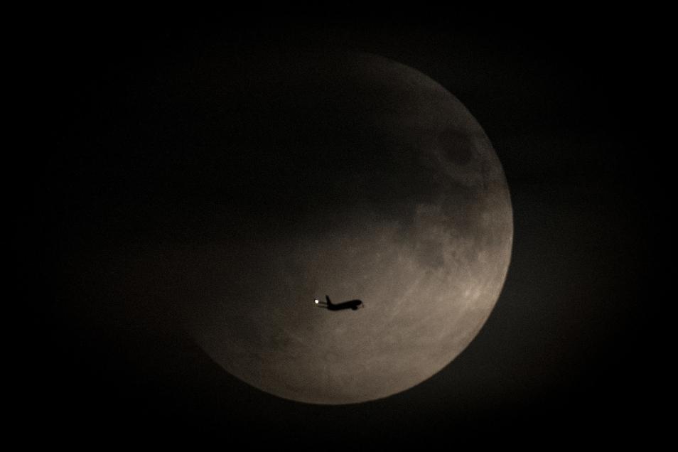 Ein Flugzeug fliegt um 22.31 Uhr am Himmel über Frankfurt/Main am Mond vorbei, der zu diesem Zeitpunkt bereits teilweise in den Erdschatten eingetreten ist.