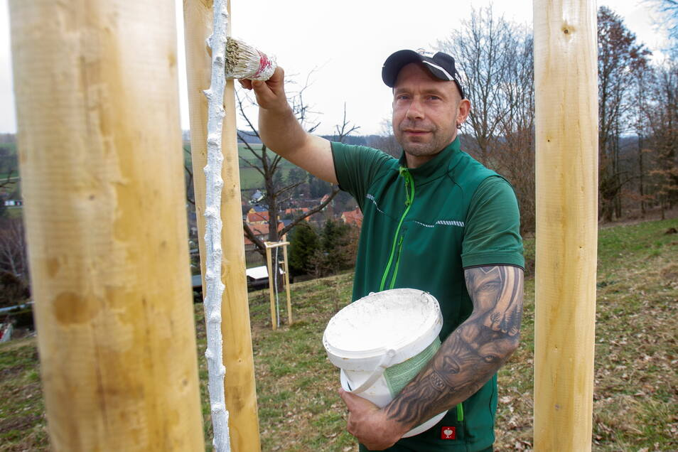 Mehr Obst für Thürmsdorf: Ralf Heidemann vom Garten- und Landschaftsbau Seiffert hat am Gartenweg neue Gehölze gepflanzt, die nun mit einer Kalkschutzschicht bestrichen werden.