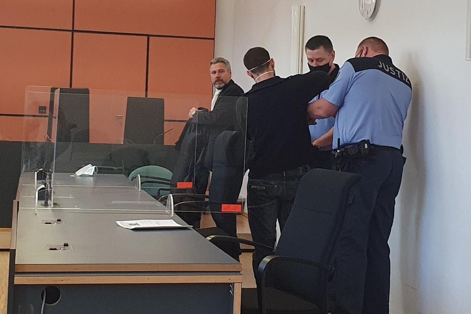 Prozessauftakt im Landgericht Dresden: Wachtmeitser nehmen dem Angeklagten Patrick K. (2.v.l.) die Handfesseln ab. Links sein Verteidiger Matthias Engel.