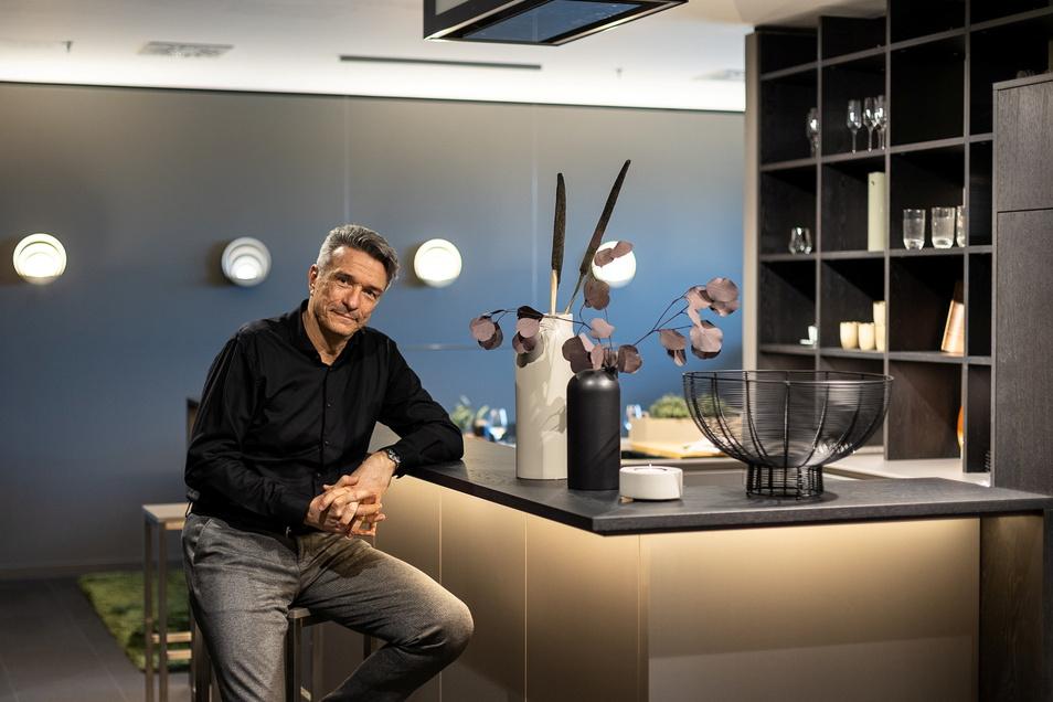 Hier sitzt Elko Beeg, der Geschäftsführer von Sachsenküchen in Obercarsdorf in einer Wohnküche in der Musterausstellung seines Unternehmens.