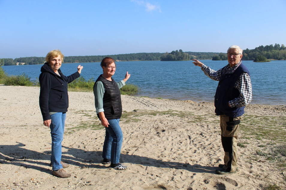 Karin (links) und Heinz Gruber aus Gröditz sowie Edith Hollas aus Großenhain zeigen auf den Strand, wo der künftige Kiessee-Besitzer Finnhütten und Zelte errichten will. Hier gehen sie im Sommer jeden Morgen schwimmen.