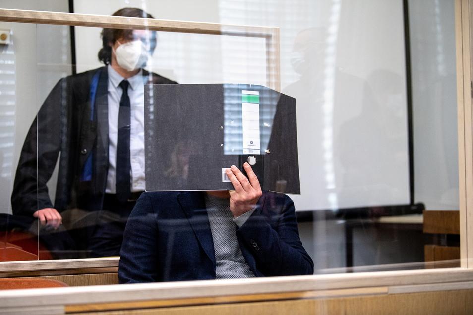 Ein wegen Verbreitung, Erwerbs und Besitzes kinderpornographischer Schriften angeklagter Mann verdeckt vor Prozessbeginn in einem Gerichtssaal vom Landgericht München I sein Gesicht mit einem Aktenordner.