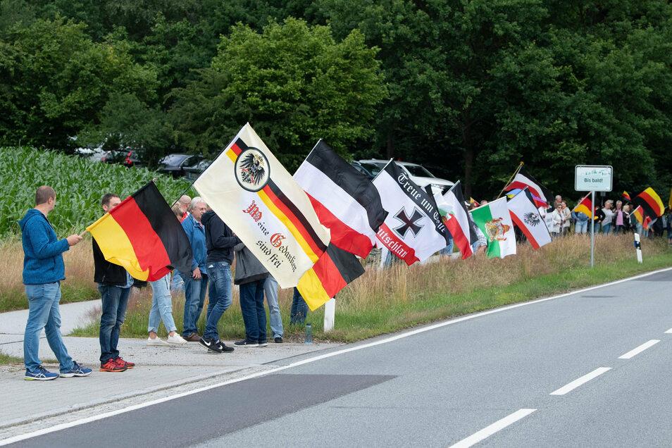 Teilnehmer eines Protests stehen mit Fahnen an der Bundesstraße 96 bei Oppach.