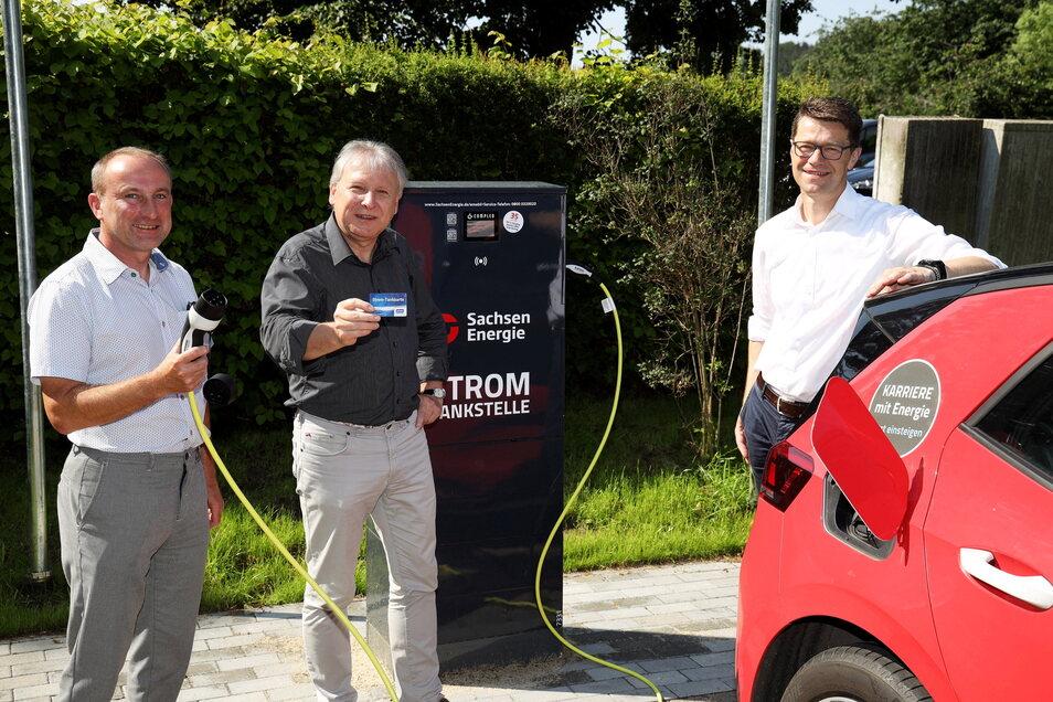 Der Nünchritzer Bürgermeister Gerd Barthold (Mitte) sowie Tilo Kadner (li.) und Gunnar Schneider (re.) von der Sachsen-Energie AG nehmen die Strom-Tankstelle auf dem Seußlitzer Schloss-Parkplatz in Betrieb.