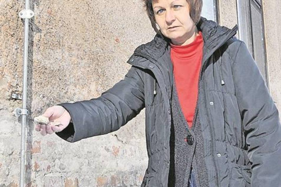 Der Putz bröckelt an der Turnhalle der Oberschule Schmiedeberg, wie Schulleiterin Katrin Jungnickel zeigt. Doch jetzt kommt der Neubau auf die Bahn.Archivfoto: Egbert Kamprath