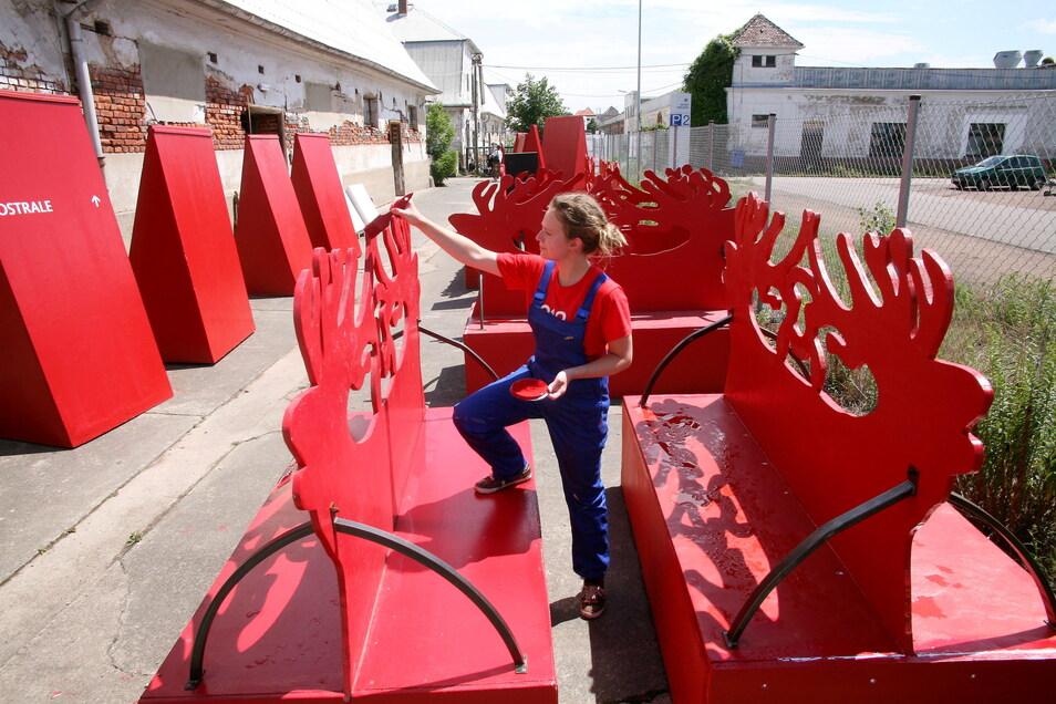 Eine Mitarbeiterin bessert die Ostrale-Wegweiser mit roter Farbe aus.