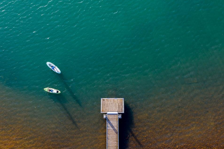 Zwei Standup-Paddler starten von einem Steg im Markkleeberger See. Das Wochenende wird vor allem am Samstag sonnig, aber es bleibt sehr kühl.