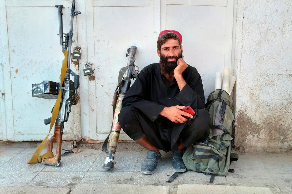 Ein Taliban-Kämpfer sitzt neben seinen Waffen. Die militant-islamistischen Taliban weiten ihren schnellen Vormarsch weiter aus.