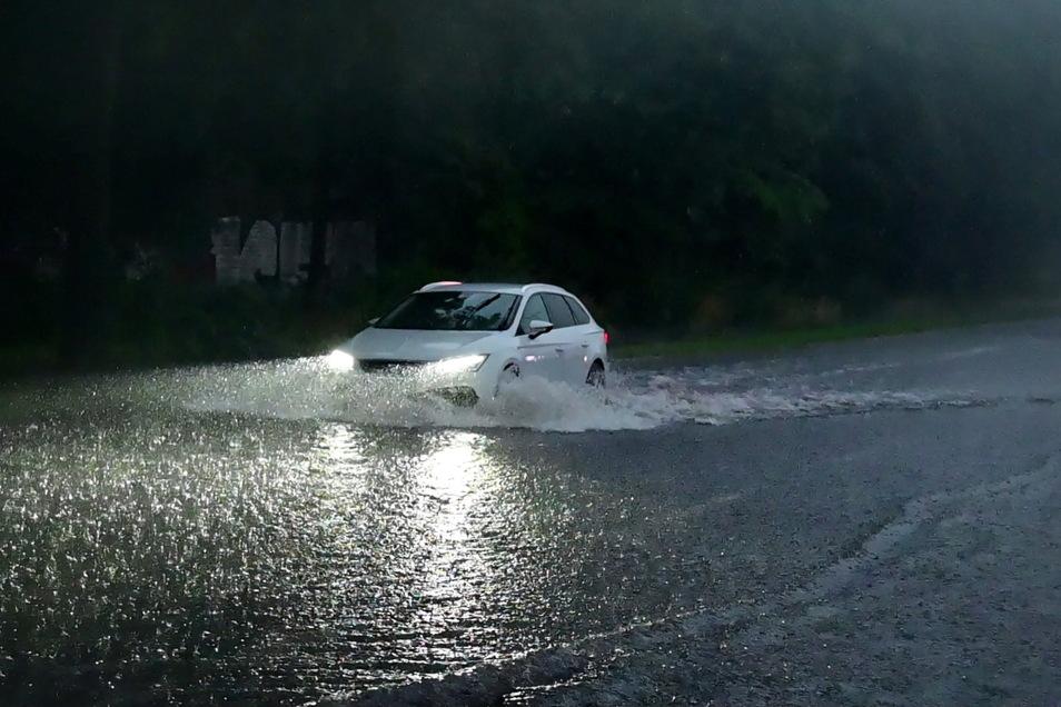 Ein Auto fährt durch eine überflutete Straße