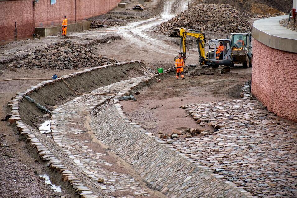 Die Mitarbeiter der Firma Swietelsky haben nach der Überflutung der Baustelle am Wochenende die Arbeiten wieder aufgenommen. Derzeit pflastern sie die Sohle des Flutgrabens.