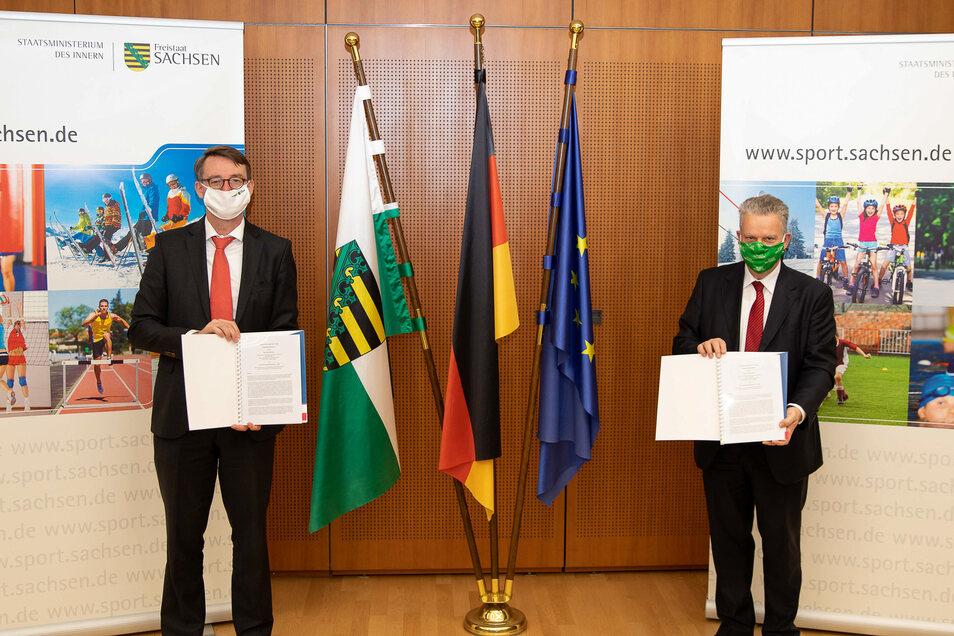 Auf Abstand präsentieren Innenminister Roland Wöller (links) und Landessportbund-Präsident Ulrich Franzen den mit Abstand besten Zuwendungsvertrag, den der sächsische Sport nun erhält.