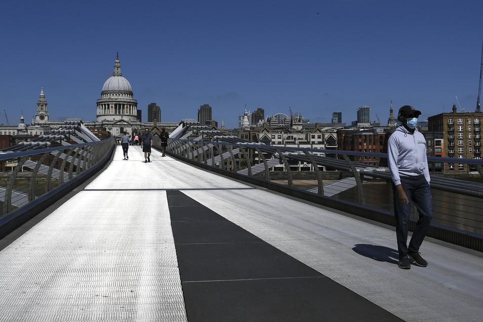 Ein Mann mit Mundschutz überquert die fast menschenleere Millennium Bridge in London.