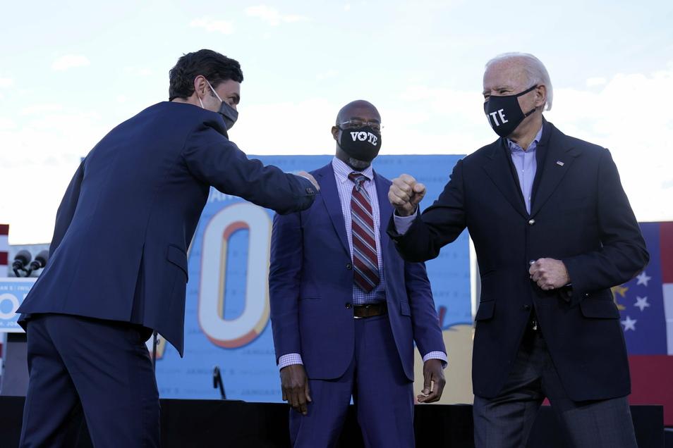 Die Demokraten Jon Ossoff (l) und Raphael Warnock (M) - hier mit Joe Biden - fordern die republikanischen Amtsinhaber David Perdue und Kelly Loeffler heraus.