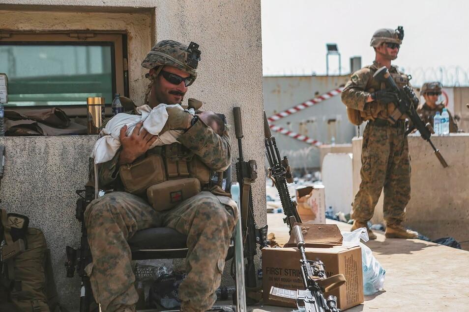 Hier kümmert sich ein US-Soldat während einer Evakuierung um ein Kleinkind.