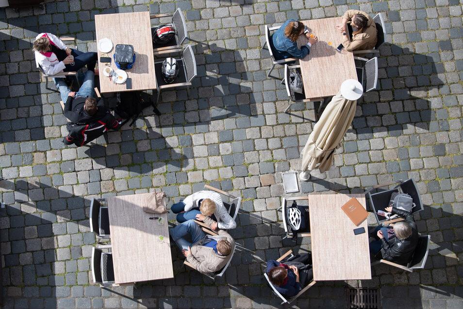Gäste sitzen am Freitag in Dresden auf dem Neumarkt in einem Cafe. Landesweit dürfen in der Corona-Krise gastronomische Betriebe wieder öffnen - das normale Leben kehrt allmählich zurück.