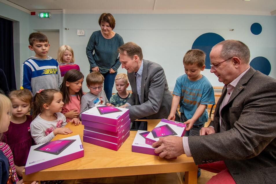 Holger Jentzsch (rechts) und Roland Pfützer von Rotary Club Döbeln-Mittelsachsen packen mit den Vorschülern der Kita Tausendfüßler die neun Tablets aus, die für ein Forschungsprojekt mit der Uni München angeschafft wurden.