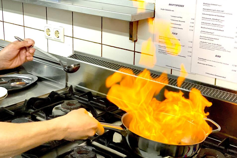 Vorsicht!! Die Flamme kann recht hoch schlagen. Wenn sie sich gelegt hat, Sahne dazugeben und aufkochen lassen. Mit Salz, Pfeffer und gehackter Petersilie abschmecken.