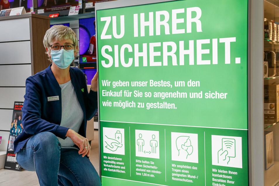 Susanne Münnich von EP Münnich in Löbau mit Maske vor einem Hinweisschild, dass im Laden Maske getragen werden muss.