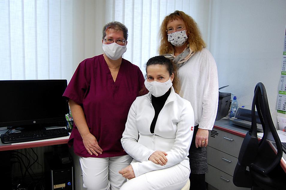 Auch sie müssen mit Mund- Nasen-Bedeckung ausgerüstet sein, wenn sie in der Anmeldung der Praxis die Patienten empfangen. Frau Dr. Elisabeth Petsch, vorn/in der Mitte sitzend, wird flankiert von Schwester Sabine (links) und Schwester Heike (rechts).