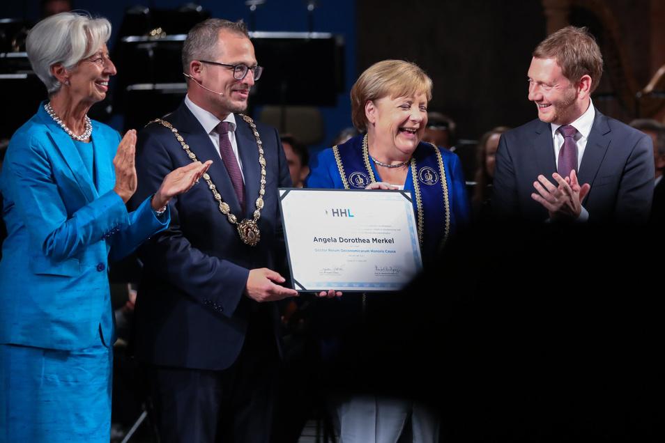 Christine Lagarde, Rektor Stephan Stubner, Angela Merkel und Michael Kretschmer in Leipzig. Mit der Ehrendoktorwürde will die Privathochschule in erster Linie Merkels Führungsstil würdigen.