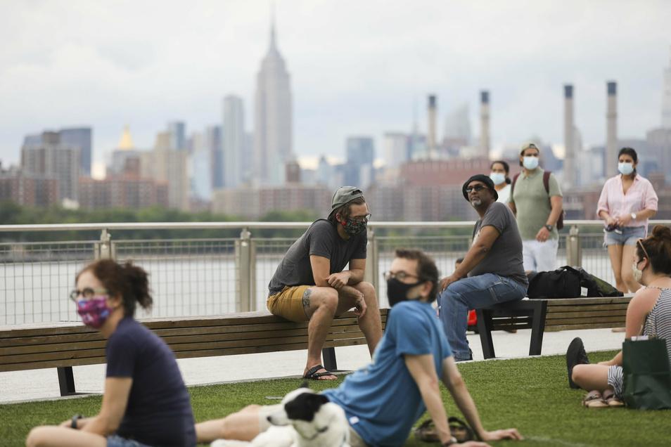 """USA, New York: Menschen sitzen im """"Domino Park"""" am Fluss East River. Die Zahl der nachweislich mit dem Coronavirus infizierten Menschen in den USA ist auf 2,6 Millionen gestiegen."""