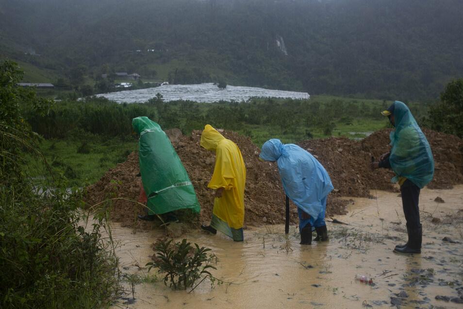 Guatemala, Purulha: In Plastiktüten und Regenmäntel umhüllte Menschen gehen um eine durch einen Erdrutsch blockierte Straße.