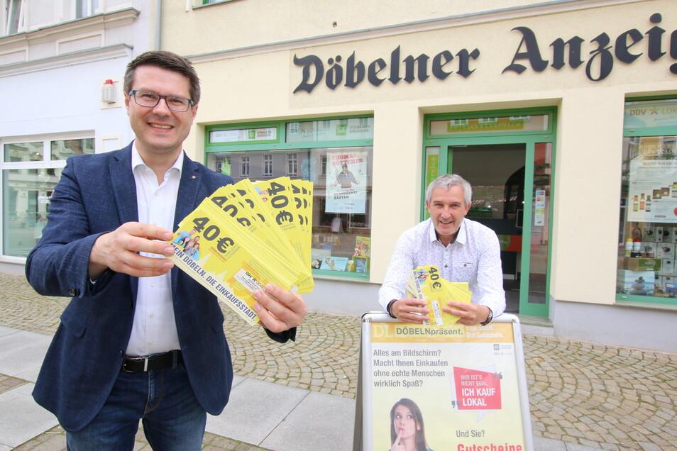 Oberbürgermeister Sven Liebhauser (links) und Matthias Poch, Geschäftsführer der DDV Döbeln GmbH, stehen mit den Gutscheinen vor dem Treffpunkt des Döbelner Anzeigers am Niedermarkt. Ab Freitag gibt es dort die subventionieren Gutscheine zu kaufen.