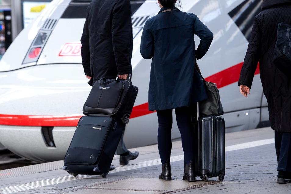 Reisende stehen neben einem ICE der Deutschen Bahn (DB). Statt im Inland zu fliegen, sollen mehr Passagiere in die Züge gelockt werden.