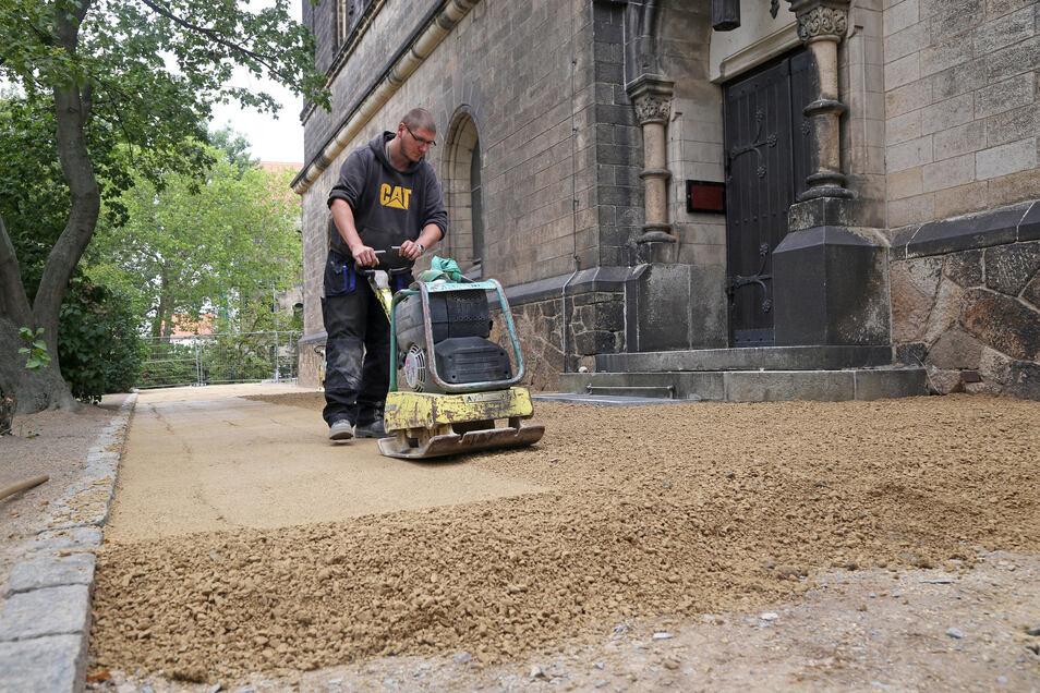 Die unterirdischen Arbeiten sind geschafft, nun werden die Spuren beseitigt. Christopher Werner von der Baufirma Otto aus Stauchitz befestigt den Weg vor dem Seiteneingang der Trinitatiskirche.