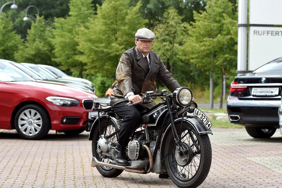 Peter Eifler in Filmklamotte auf seinem historischen BMW-Motorrad.